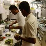 Abschauen und lernen: Rupan (vorne) richtet unter Anweisung seines Arbeitskollegen Salate an.